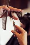 Hairdresser is straightening hair - 173879452