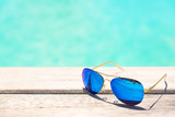 Blue sunglasses lying on a wooden deck by turquoise sea water, selective focus