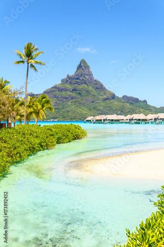 Foto Murales View on Mount Otemanu through turquoise lagoon and overwater bungalows on the tropical island Bora Bora, Tahiti, French Polynesia, Pacific ocean.