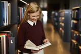 beautiful woman reading book in library, smiling - 173897012