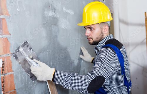 Smiling workman in the helmet is plastering the wall © JackF