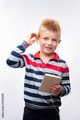 Póster Cute little boy listening to music and holding notebook