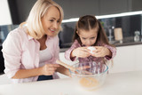 The grandmother teaches the girl how to break the eggs. The girl is holding an egg in her hands over a glass bowl - 173927285