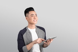 Confident young asian businessman holding digital tablet looking up - 173934256
