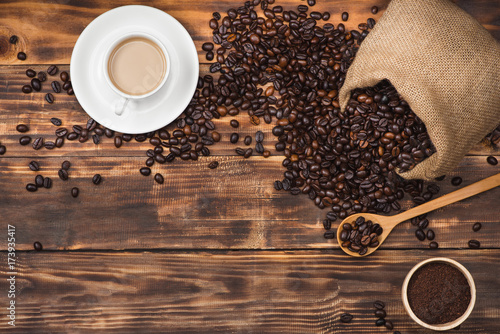 Coffee beans in spoon and cup of hot drink Poster