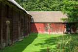 Two barns meet in the corner of a farm yard. - 173942490