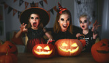 family mother and children in costumes and makeup to halloween with pumpkin in   dark - 173947891