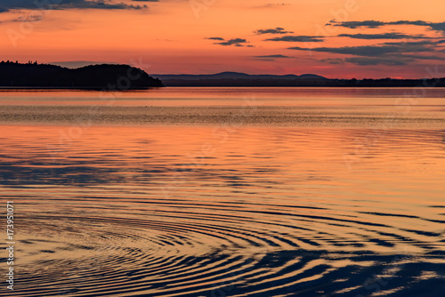 In de dag Koraal sunset over the transylvania lake in Umbria Italy intense late summer colors in the pier