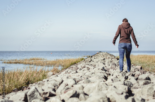 Tuinposter Noordzee Spaziergang auf dem Damm an der Nordsee