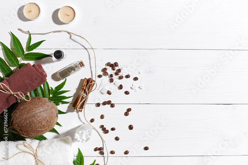 Natural spa set with candles, coffee beans, cinnamon, sea salt, oil, brown towel, coconut and green leaves on white wooden background © nazarovsergey