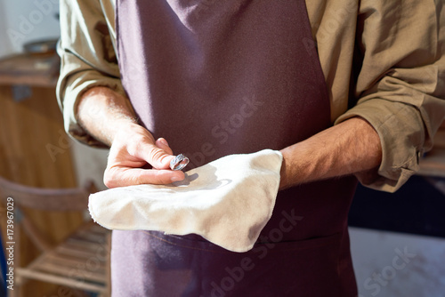 Mid section portrait of unrecognizable jeweler presenting newly made precious ring on cloth in his hands © seventyfour