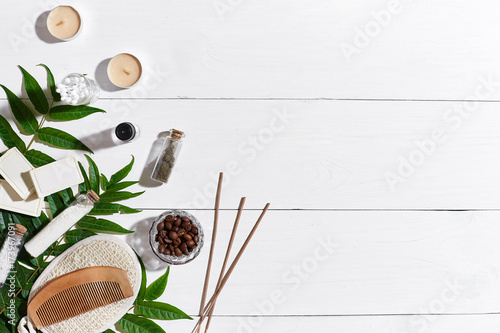 Natural handmade soaps with coffee beans, sea salt, loofah, brown towel and green leaves on white wooden background © nazarovsergey