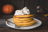 Pumpkin pancakes stack served with whipped cream, pecan nuts and cinnamon. Closeup view, horizontal, toned image - 173983886