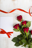 Composition of red roses, card and ribbon