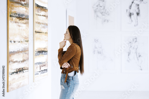 Poster Young woman observing painting