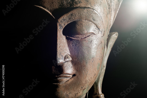 Papiers peints Buddha Spiritual enlightenment. Buddha head with divine light. Bronze statue face in close up.