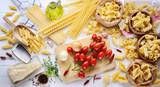 Pasta and ingredients: tomatoes, parmigiano, extra virgin, pens, shells, rigatoni, mafalda, linguine, fusilli and squid - 174028604