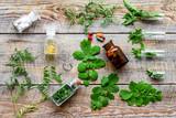 Herbal medicine. Leaves, bottles, pills on wooden background top view