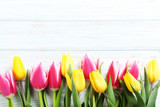 Bouquet of bright tulips on white wooden table - 174062040