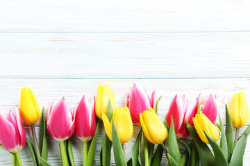 Bouquet of bright tulips on white wooden table
