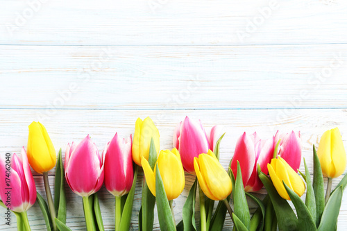 Fototapeta Bouquet of bright tulips on white wooden table