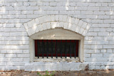 Small arched basement window with bars in a white brick wall