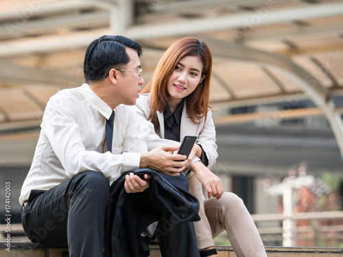 Two of asian businessman businesswoman sitting at stair discussing about business plan for future in the modern city, casual business concept