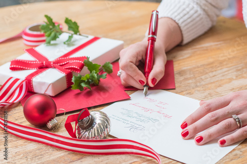 Young woman writing christmas cards with red nails a red pen and young woman writing christmas cards with red nails a red pen and holiday decorations m4hsunfo