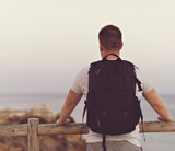 Male tourist with backpack looking at the ocean. - 174167437