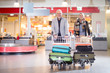 Happy Senior Business Couple With Luggage In Carts At Airport - 174178032