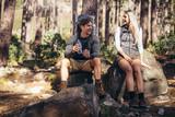 Hiking couple relaxing sitting on rocks during trekking - 174181618