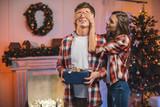 woman surprising boyfriend on christmas - 174192052