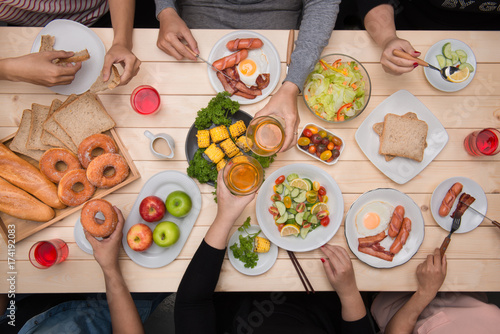 Enjoying dinner with friends.  Top view of group of people having dinner together while sitting at wooden table - 174192083