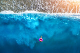 Aerial view of slim woman swimming on the pink swim ring in the transparent turquoise sea in Oludeniz,Turkey. Summer seascape with girl, beautiful waves, blue water in sunny day. Top view from drone - 174220876