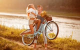 young couple in love riding a bike near the river in the summer at the weekend - 174224611