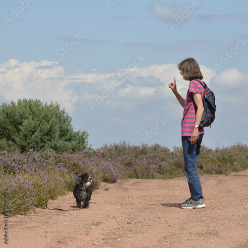 Fotobehang Zalm eine frau steht in der mehlinger heide und gibt ihrem hund anweisungen