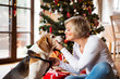 Senior woman with dog in front of Christmas tree