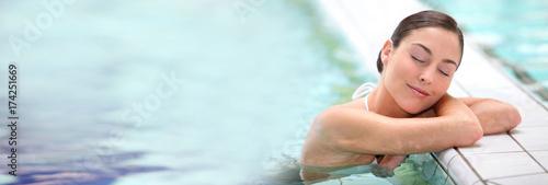 Foto Murales Beautiful young woman relaxing in seawater pool