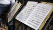 Dettaglio di uno libro di musica poggiato su un leggio nero durante un concerto. Le pagine sono aperte e lo spartito e le note sono ben visibili.
