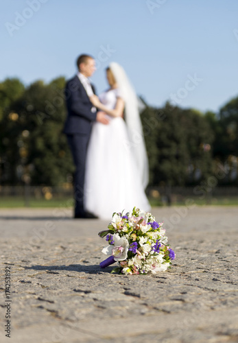 bride and groom on the street, the wedding, the Bridal bouquet on the pavement,