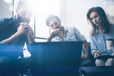 Teamwork process concept.Young coworkers work with new startup project in office.Horizontal, blurred background. Flares.