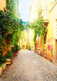Fototapeta Uliczki - view of old town italian narrow street with blue sky in Trastevere, Rome, Italy, retro toned © neirfy