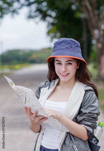 A pretty traveling woman reading a map