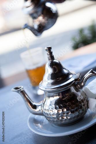 Fotobehang Marokko Marokkanischer Minz Tee Kanne und Teeglas im Straßencafe