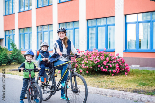 Family cycling, mother with happy kid riding bike outdoors