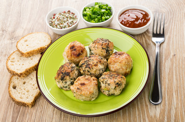 Fried meatballs in green plate, ketchup, green onion, bread