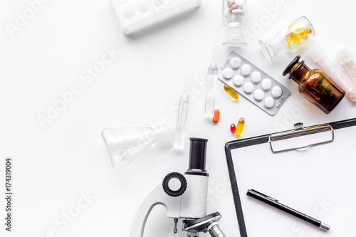 Do medcal tests. Microscope, tablet, pills on white background top view copyspace