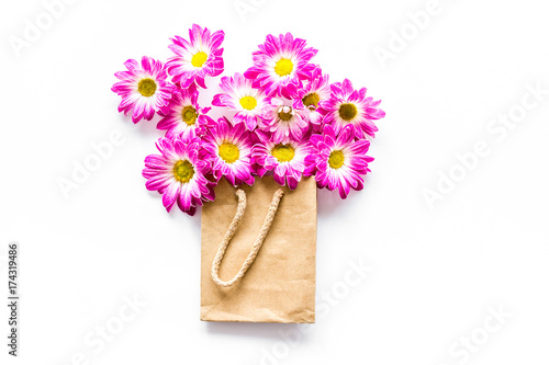 Fototapeta Floral pattern. Bouquet in a paper bag on white background top view copyspace