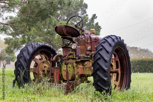 Fotobehang Trekker Old abandoned tractor sitting in the rain
