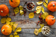 Quadro Pumpkin harvest. Pumpkins near nuts and autumn leaves on wooden background top view copyspace